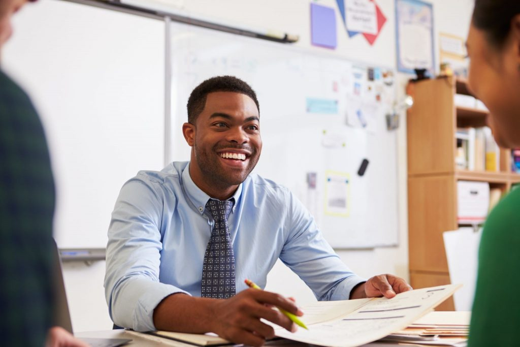 Happy teacher at desk talking to adult education students