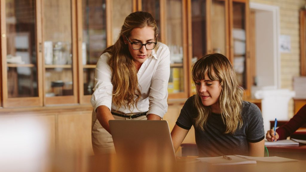 Teacher assisting the problem of a student in her classroom.