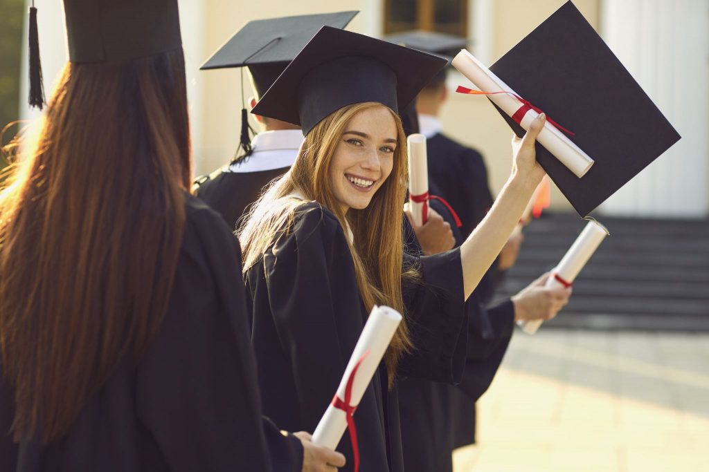 confident graduate student holding diploma while standing with friends at university