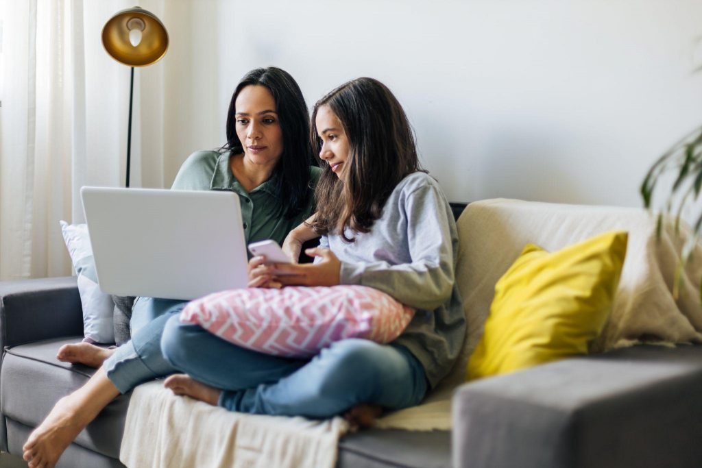 mother working from home with preteen daughter around