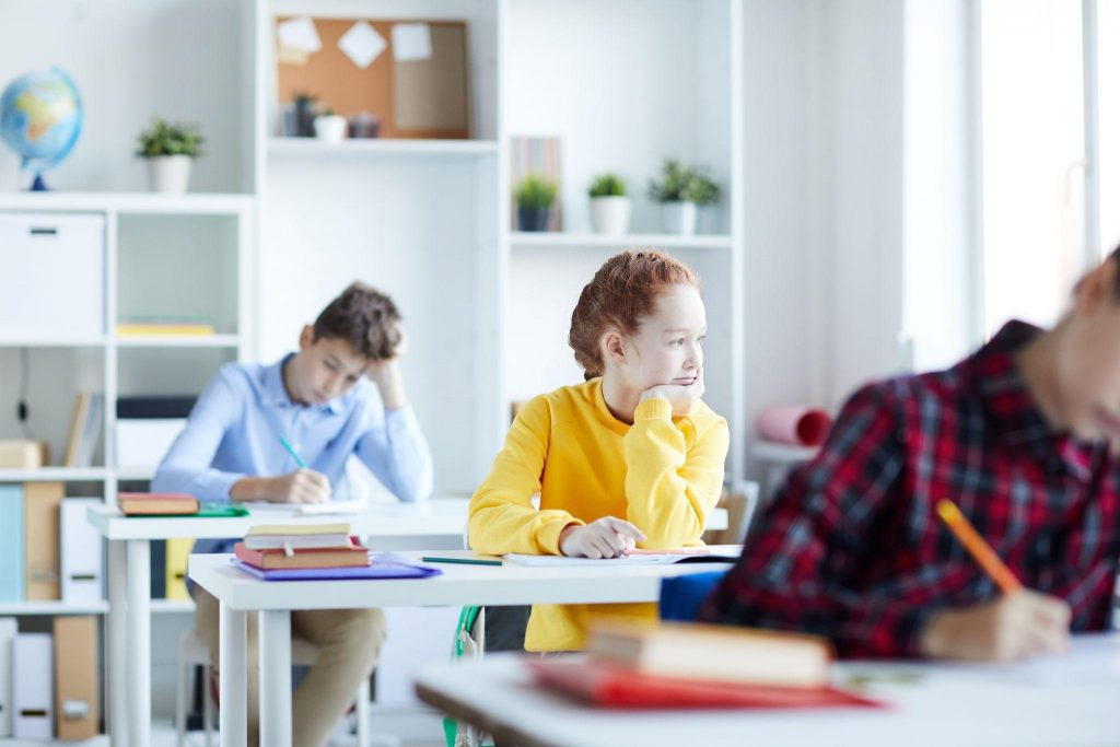One of schoolkids sitting by desk among classmates and looking through classroom window